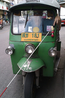 Mike using cane to drive the Tuk Tuk in Bangkok