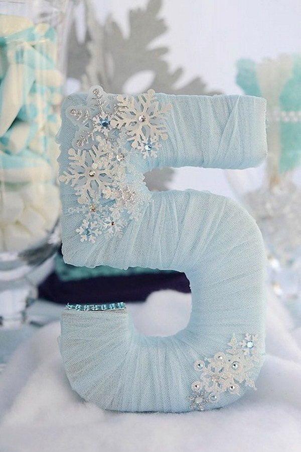 Faça estas lindas tules embrulhadas para uma festa temática da Disney! Basta comprar um número de madeira e encapar com tecido e depois decorar com fractais de gelo que podem ser encontrados em lojas de artigos para natal ou festas.