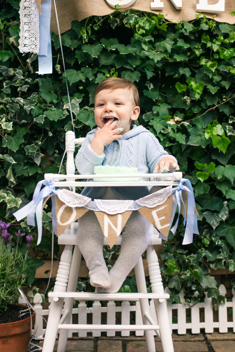 Baby cake smash in vintage baby high chair with bunting for babys Peter Rabbit themed first birthday