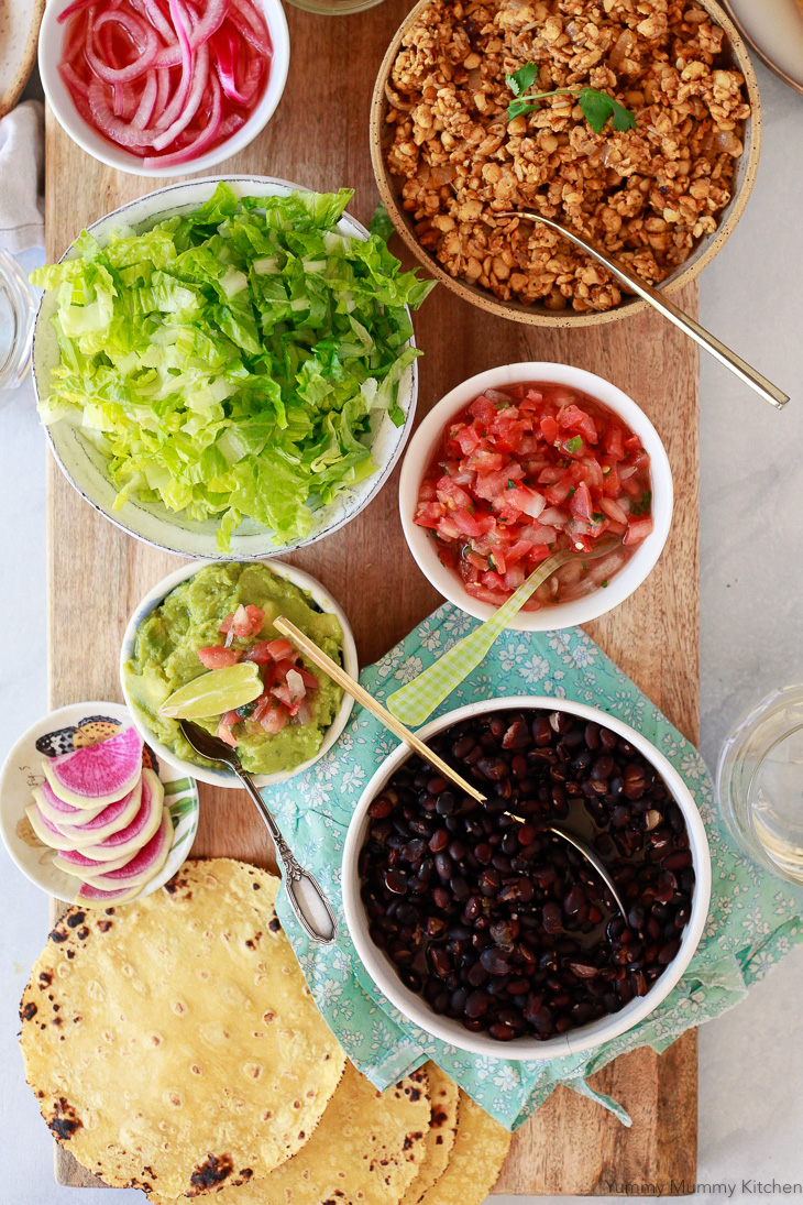 Tempeh taco filling along with black beans, salsa, guacamole, and lettuce on a long serving board.