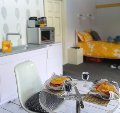 One-twelfth scale modern miniature motel room with a kitchenette at the front with a round table set for fish and chips and red wine. At the back of the room is a bed and bedside table.
