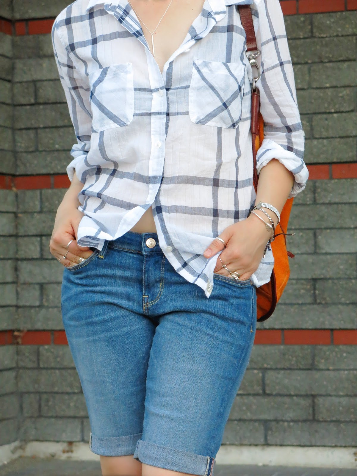 a white plaid shirt, denim bermudas, and orange suede bag