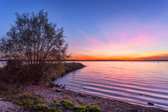 The reservoir at Grafham Water ripples gently under the vibrant sunset sky