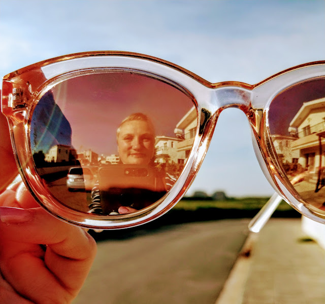 photograph showing photographer in reflection in mirrored sunglasses