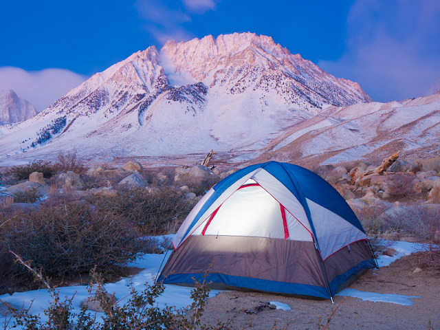 A tent with a frosty mountain in the background