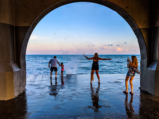 group standing on edge of breakwater being sprayed with waves
