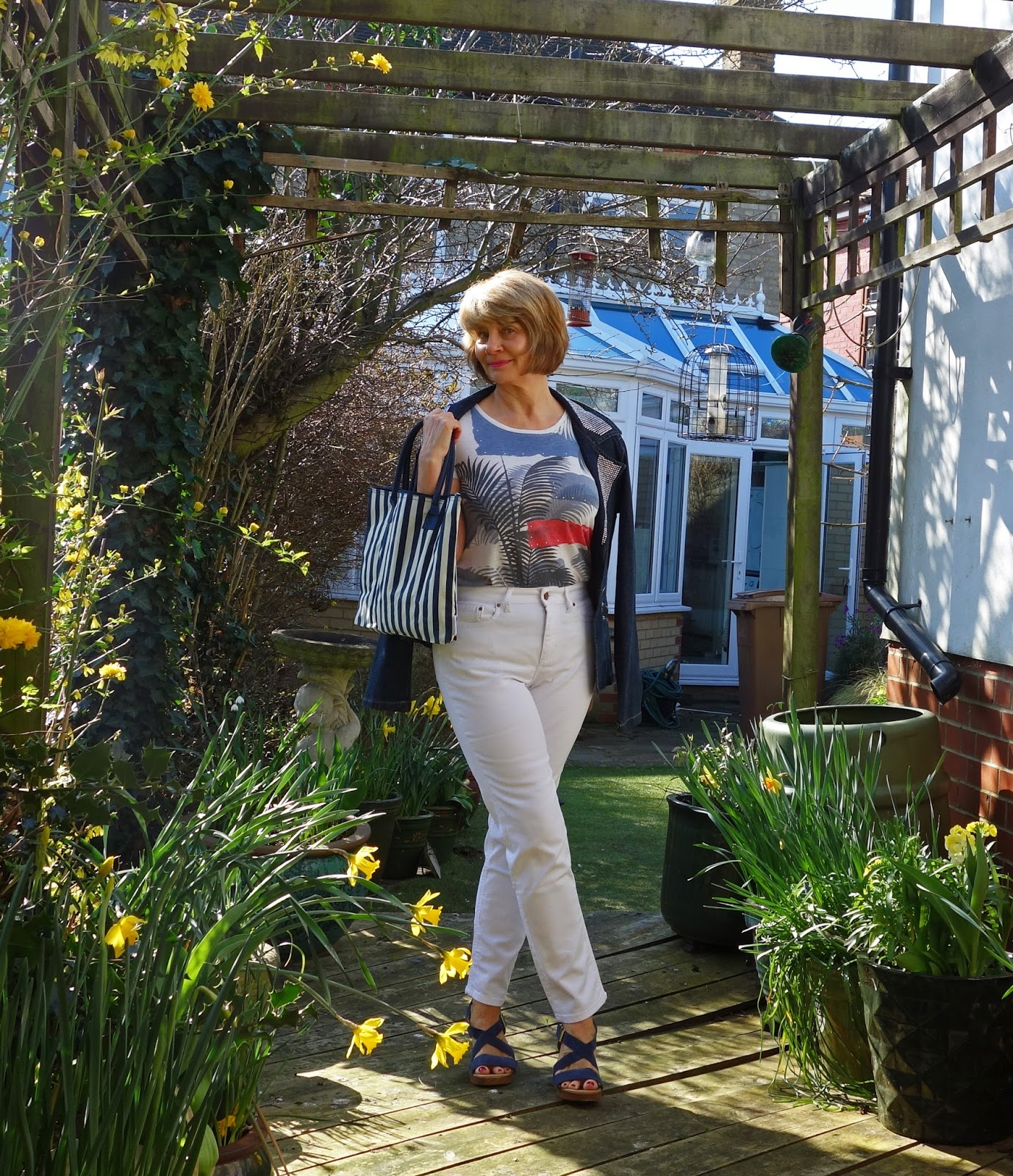Image showing woman wearing Dolce and Gabbana denim jacket, white jeans and stripy bag