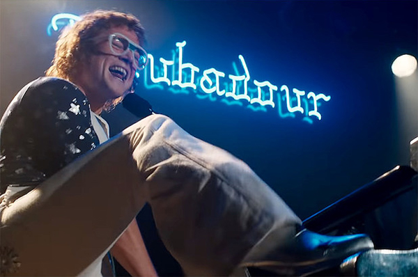 image of Taron Egerton as Elton John in 'Rocketman,' playing and singing with his foot on the piano keyboard at the Troubadour