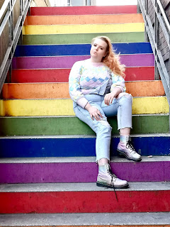 A mid shot of Michelle posing with a blonde ponytail wearing a beige jumper, light blue pants and sparkly silver Doc Martens spread out on a rainbow staircase