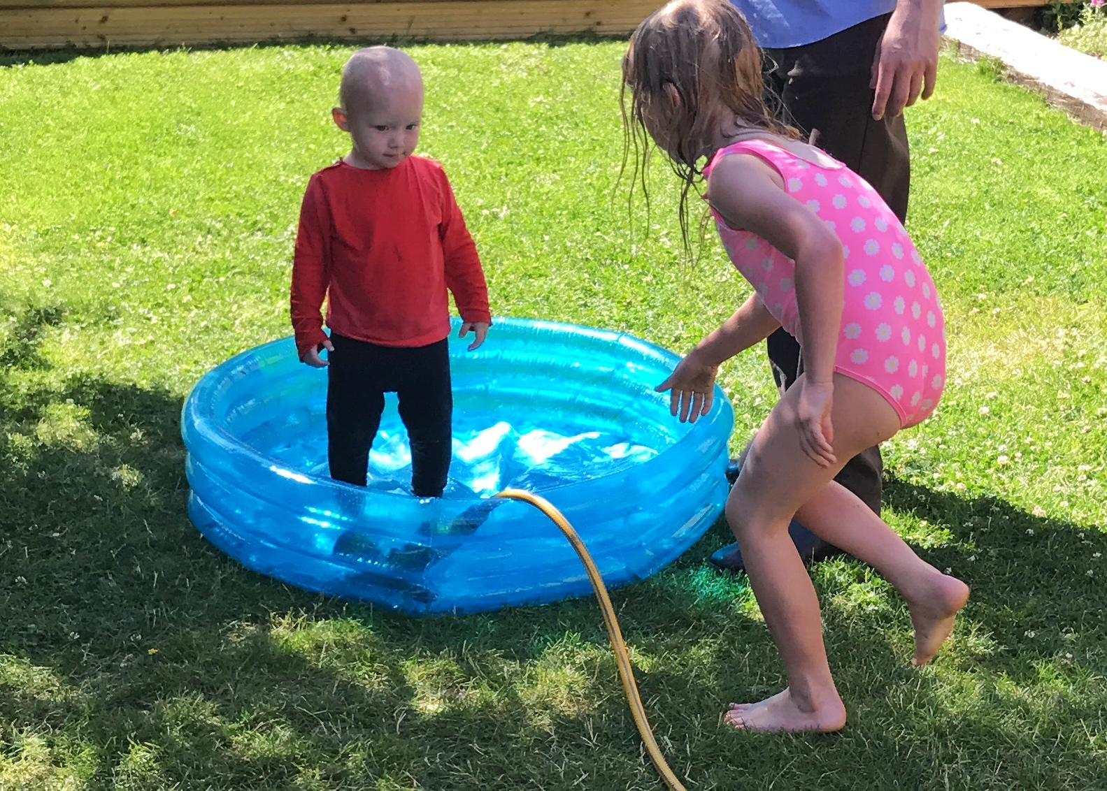 Filling a small paddling pool with a hose while a toddler stands in it fully clothed