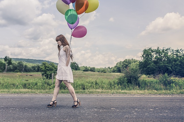 Woman Walking Alone with Balloon Tied to Her Arm