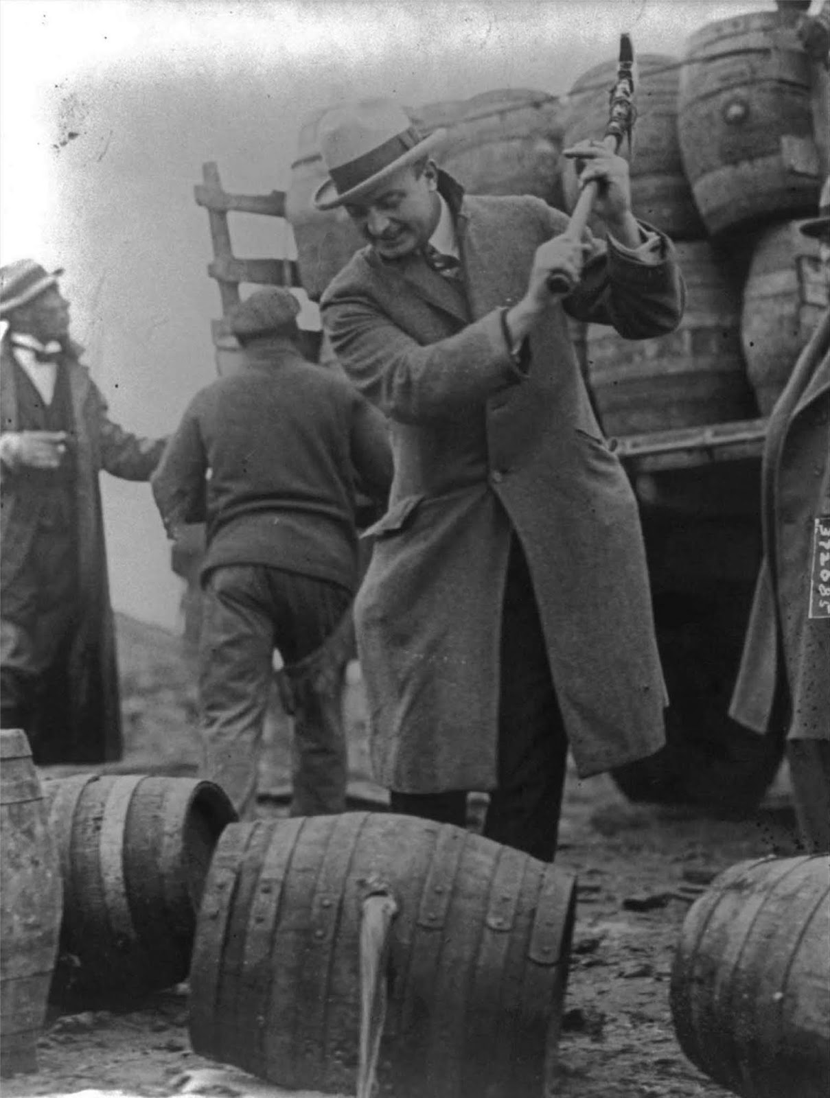 An FBI Officer breaks a confiscated barrel of beer. 1924.