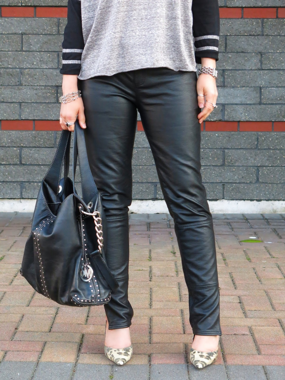 styling vegan leather jeans with a long-sleeve baseball tee and animal-print pumps