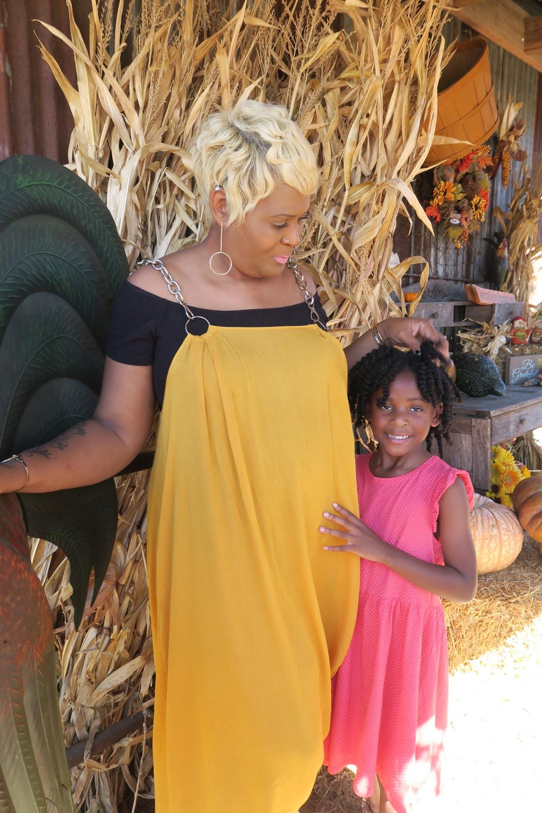 Image: Mother and daughter pose at Hall's Pumpkin Patch. Mom is sharing their fall family traditions and date ideas.