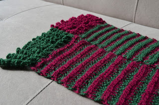 Looking down and across the ends of the scarf as it rests on a flat surface. The far section is mainly green with red accents and a red fringe. The colours are vice versa for the front section. One can see the Main Colours of each section form dominant ridges in the fabric.