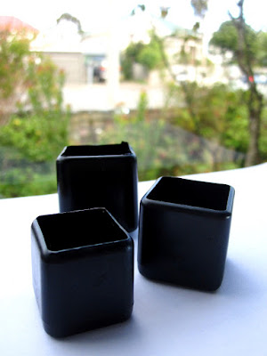 Three different-sized square black modern dolls' house miniature plant pots.
