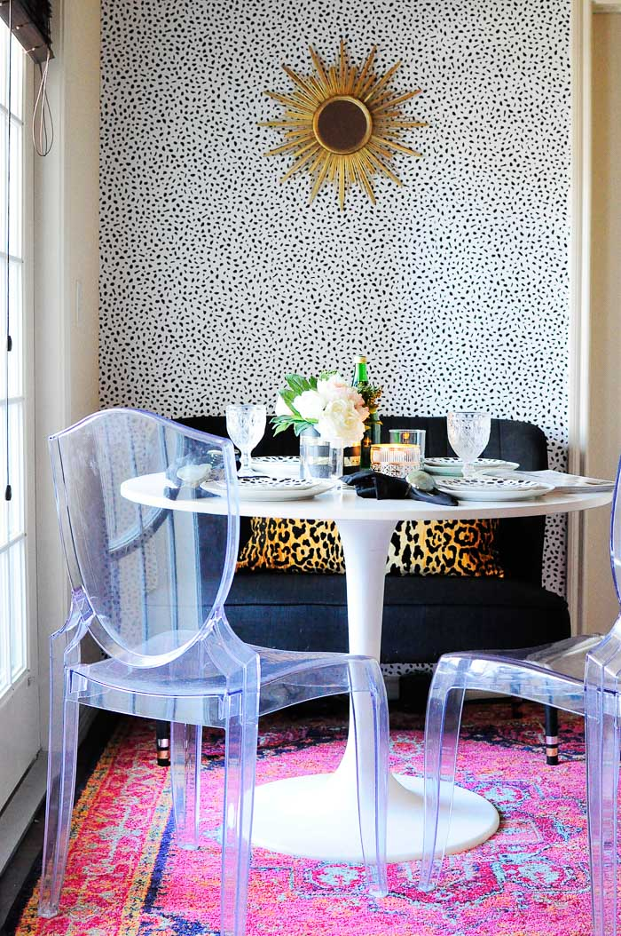 A boring and small 9x6 beige dining space in an apartment gets a glam makeover! No paint or power tools were needed, but the end result is gorgeous. Tanzania inspired spotted wallpaper, IKEA docksta table, bright pink rug and more.