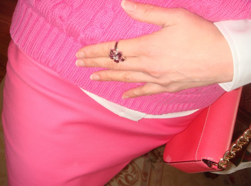 All pink outfit, middle body shot showing hand with purple stone flower ring.