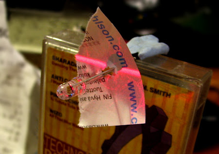 [Image: A photodiode attached to a cassette case using blu-tack. A piece of paper is attached to the base of the diode, and a line of red laser light is visible on the paper, also hitting the diode.]