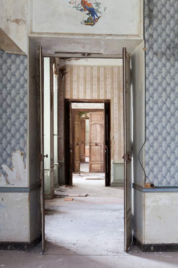 Stripped blue tufted wallpaper decay inside French Chateau Gudanes