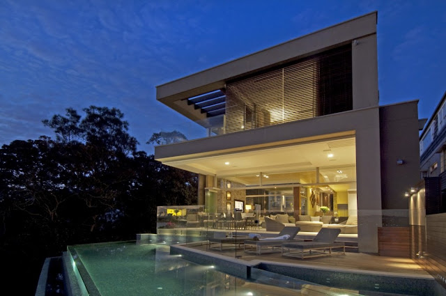 Modern home with its swimming pool and terrace from the backyard