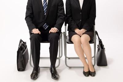 リクルートスーツを着た就職活動中の男女二人が面接官の前で座っている