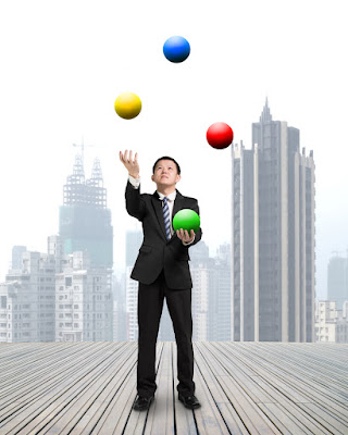 A businessman is juggling 4 colored balls