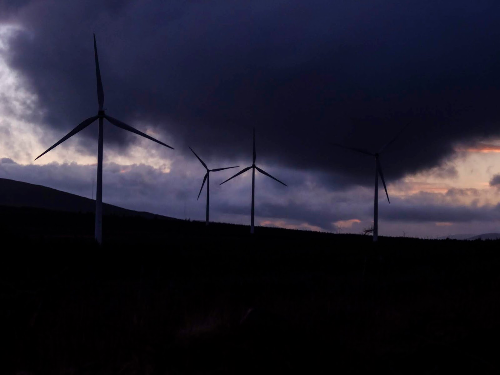 Dark sunset clouds behind windmills in the mountains.