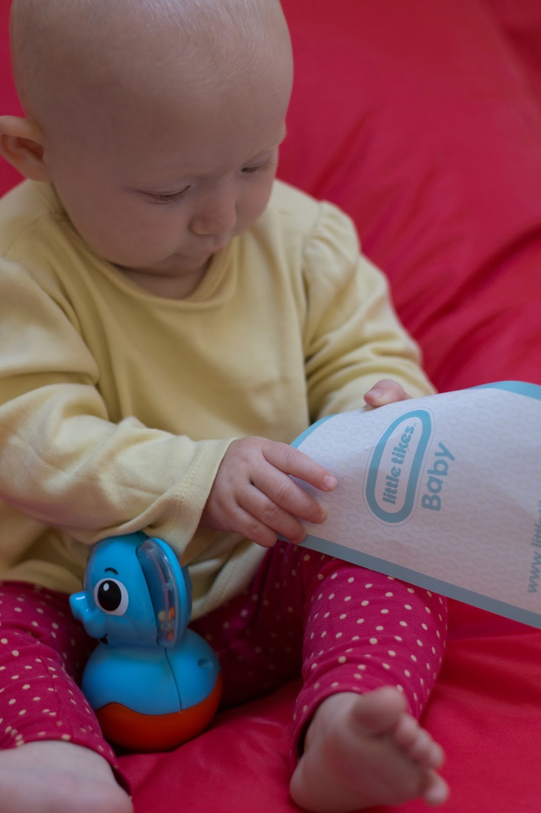 A baby on a big red bean bag holding a baby milestone card with an elephant rattle toy between her legs