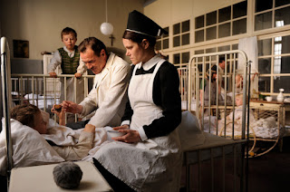 A nurse (Henriette Confurius) hands a drink to a boy in a hospital bed. Courtesy of StudioCanal.