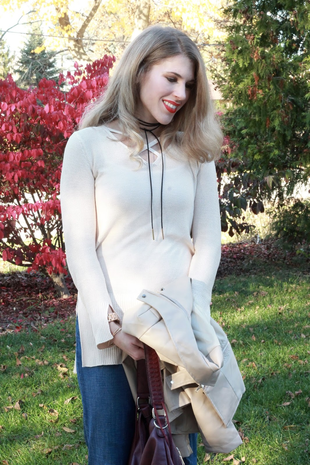 beige khaki moto jacket, ivory criss cross tunic sweater, flare jeans, blush heels, burgundy purse