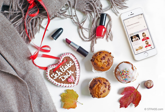 This picture shows a Wiesn themed Flatlay with some dark lipsticks, red nailpolishes, cupcakes and a mobile phone showing our Pinterest board about the perfect Wiesn hairstyles.