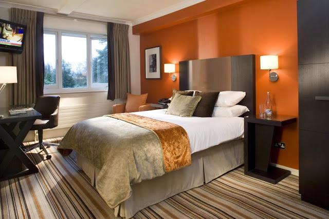 kamar dengan warna orange kasur warna putih didinding warna putih