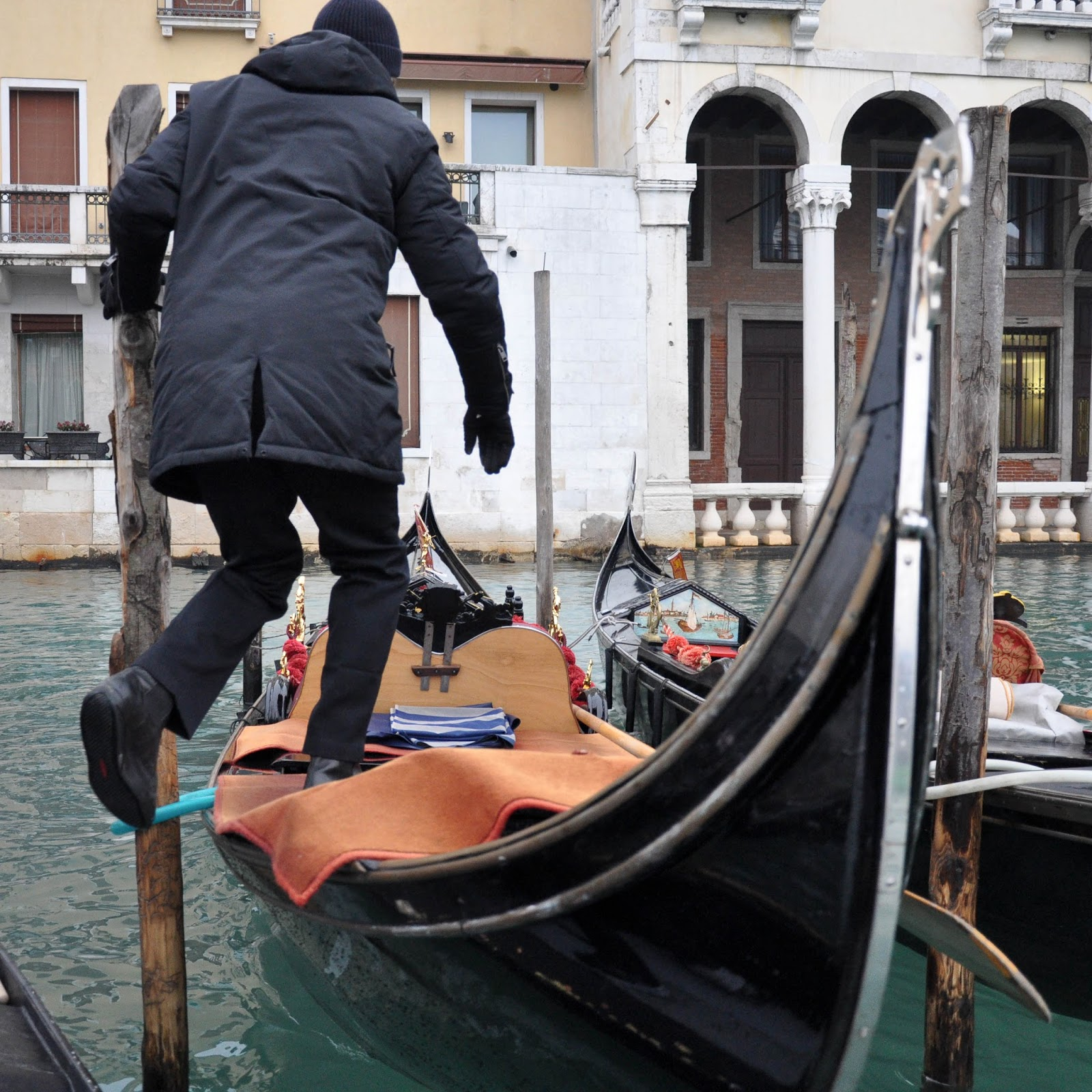 A gondolier gets on his gondola from a traghetto, Venice, Italy