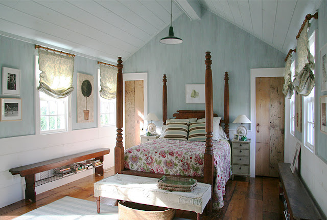 Elegant country bedroom with wood walls painted blue in Barn conversion home by Carrier and Company