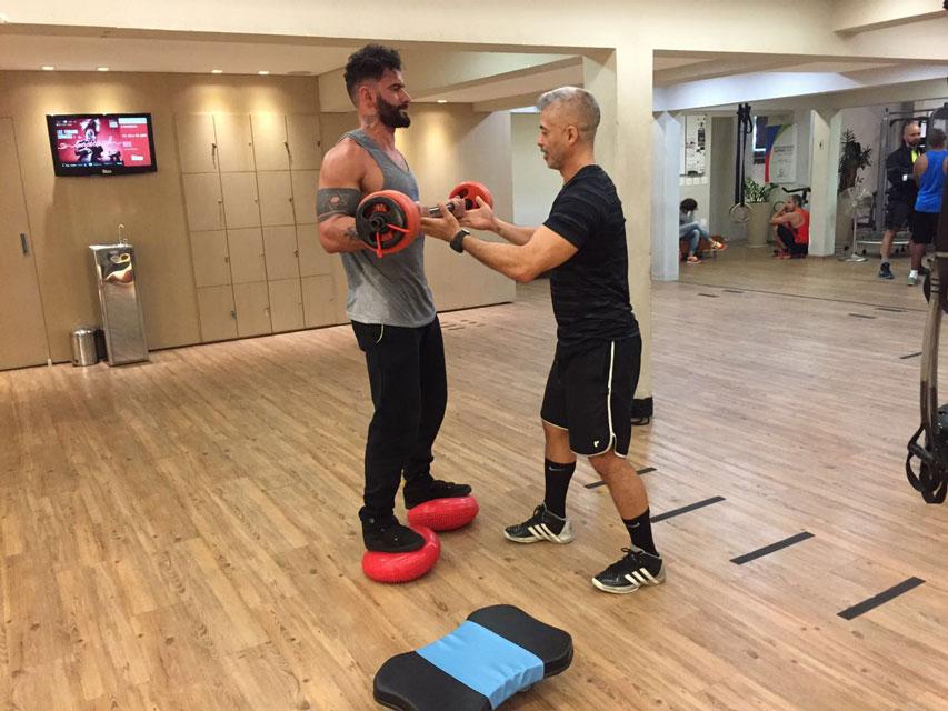 Cleverson Fontinatte realiza exercício rosca bíceps sobre disco balance sob a supervisão do educador físico Kenji Takahashi. Foto: Divulgação