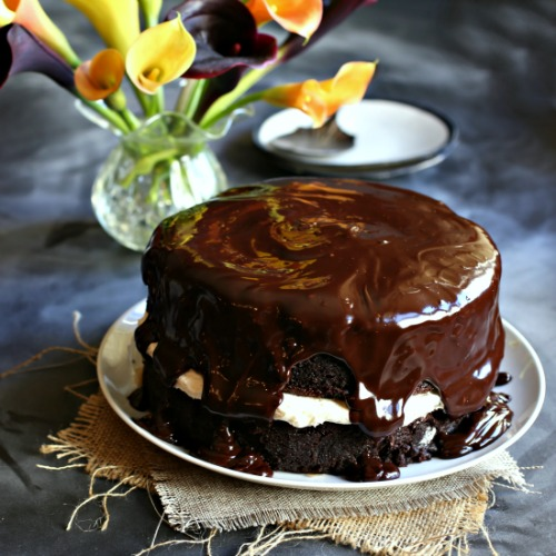 Rich, two layer deep chocolate cake with a flavorful pastry cream in the center and chocolate ganache on top.