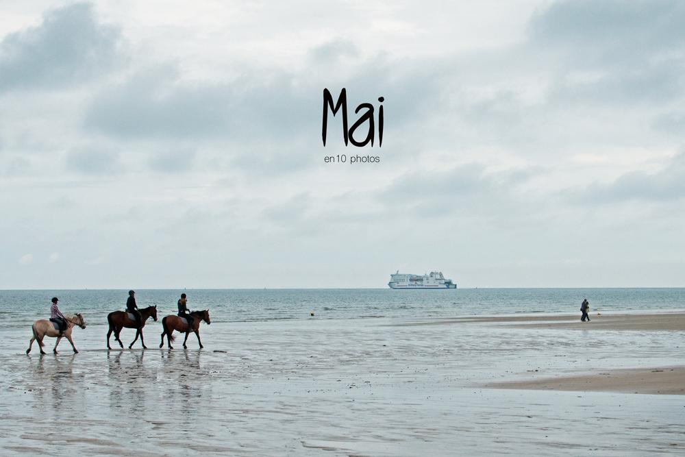 Vue de la plage de Ouistreham par temps couvert. On aperçoit le ferry qui part ainsi qu'un couple enlacé et 3 chevaux qui avancent au pas