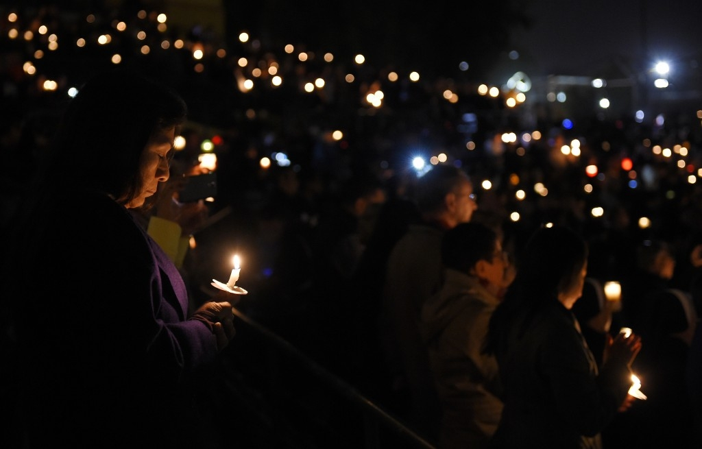 70 Of The Most Touching Photos Taken In 2015 - People hold a candlelit vigil for victims of the San Bernardino shooting at San Manuel Stadium.