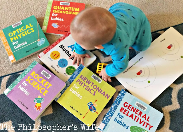 A baby is crawling among a variety of books, including Optical Physics for Babies, Quantum Entanglement for Babies, Rocket Science for Babies, Newtonian Physics for Babies, and General Relativity for Babies.