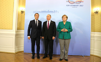 Vladimir Putin with Federal Chancellor of Germany Angela Merkel and President of France Emmanuel Macron before a working breakfast.