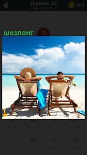 На берегу солнечного моря двое сидят в шезлонге и загорают в шляпах