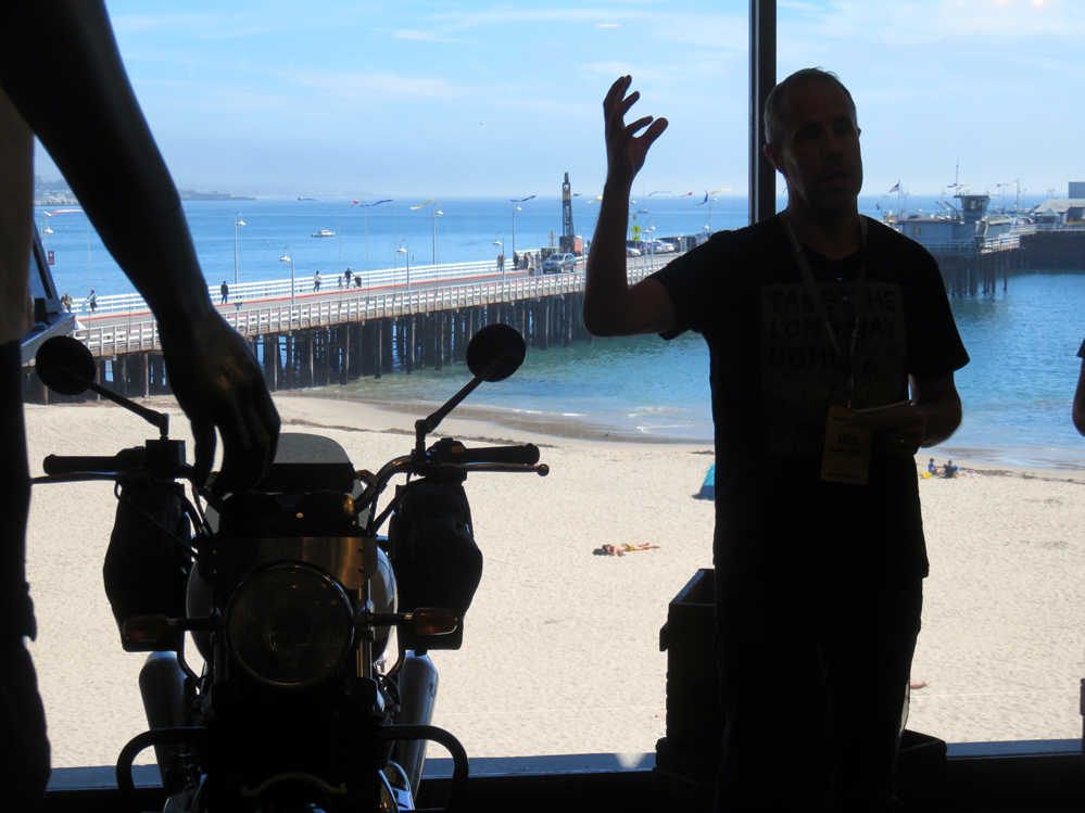 Man talking in front of window with beach outside.