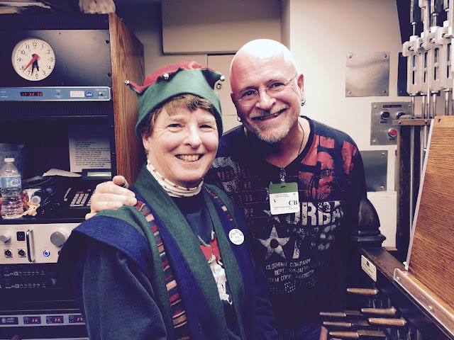Andrea McCrady (in Christmas garb) poses with Pierre Massie in the playing room