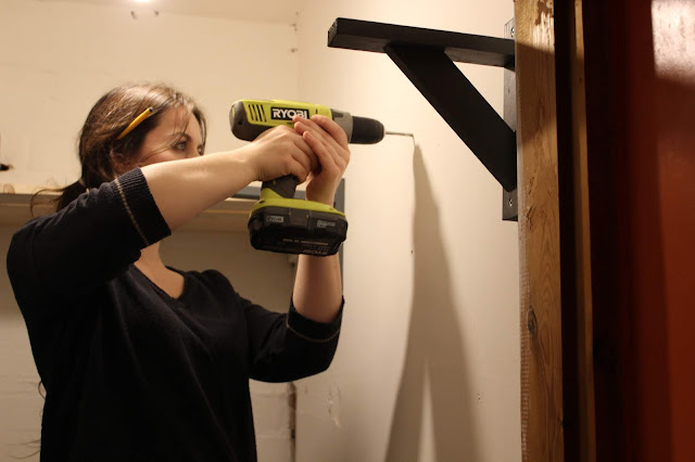 woman fitting shelf brackets DIY