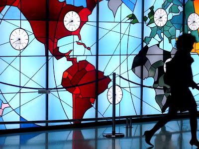 Uhren auf einem von hinten erleuchteten Glasmosaik, das die Kontinente darstellt. Ein weiblicher Schattenriss eilt aus dem Bild.