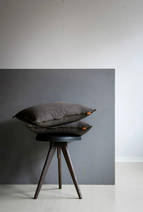 Vor einer grauen Wand steht ein schwarzer Hocker, auf dem braune Kissen gestapelt sind