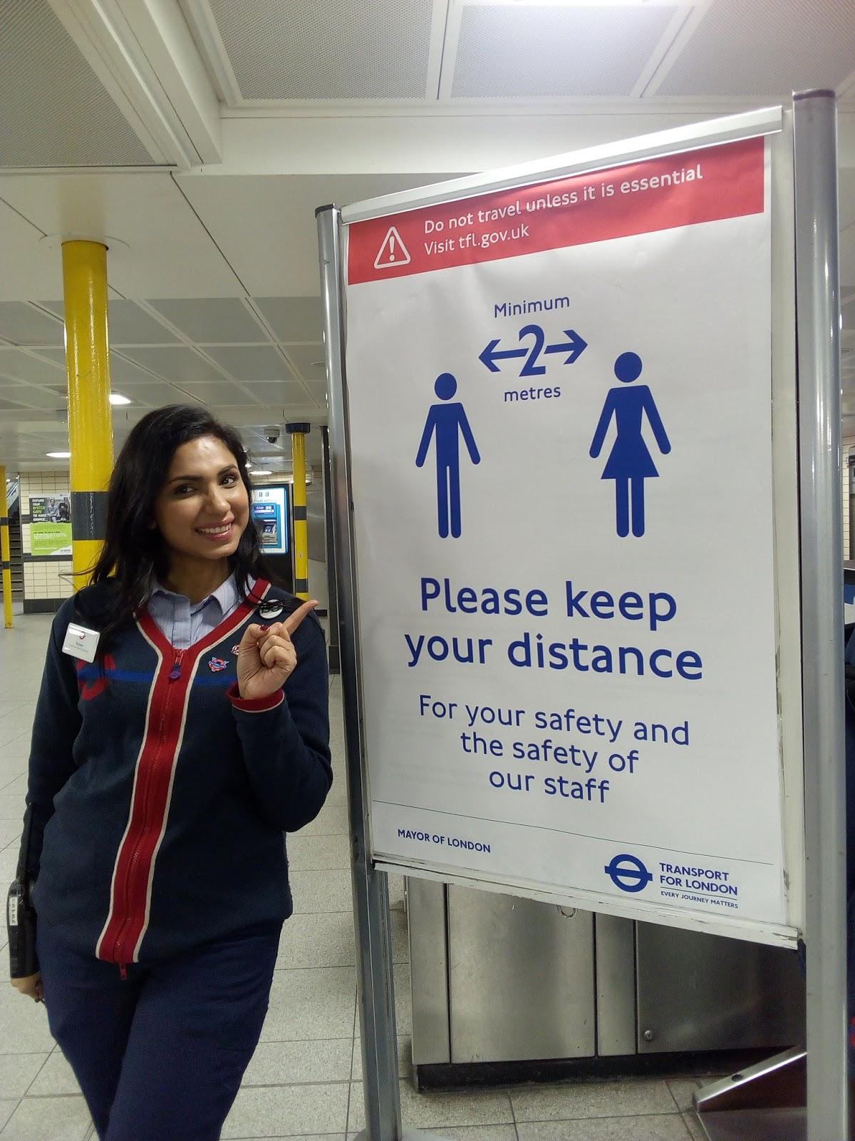 Metro darbiniece norāda uz plakātu par sociālo distancēšanos
