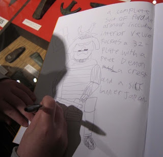 Photograph of student making drawings of Museum objects in his sketchbook