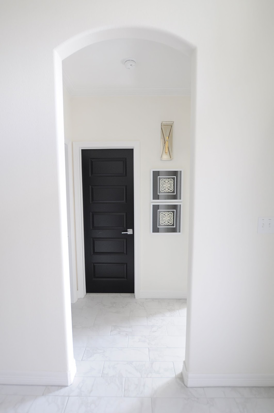 Black interior doors with white walls and a chrome and gold hallway sconce under an archway.